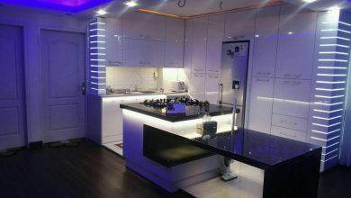 Photo of آشپزخانه مدرن سفید با نورپردازی ویژه و سنگ کورین مشکی